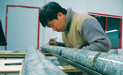 Examining core from the Zuun Mod project. Photo from Erdene Resource Development Corp.