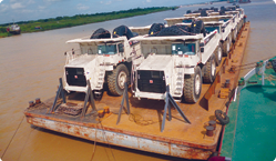 Ten of the Terex Trucks loaded on a barge for transport along the Uru River.